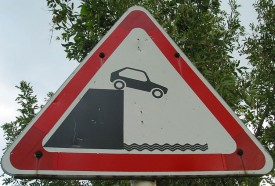Street sign of a car going off a cliff